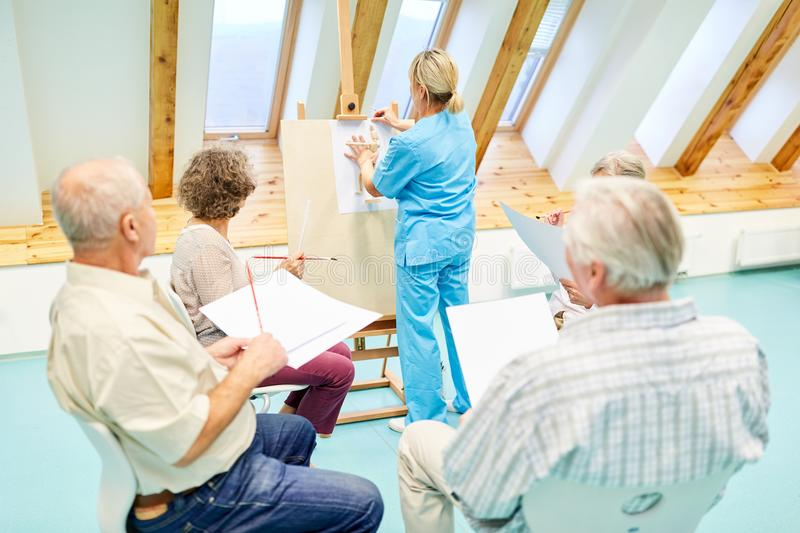 Caregiver and seniors in the drawing class stock photography