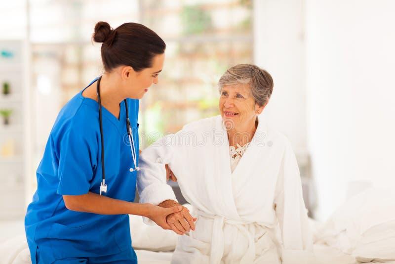 Caregiver die oudste helpen stock foto