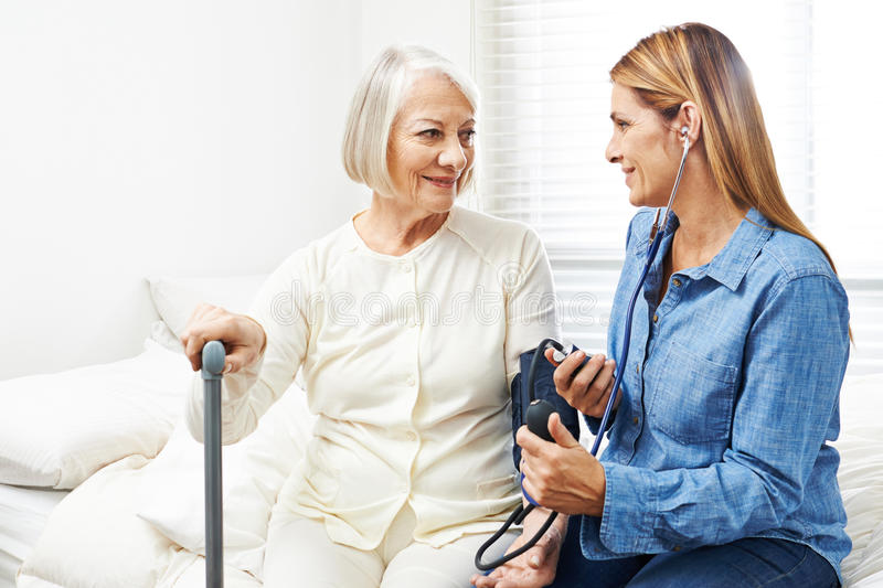 Caregiver doing blood pressure monitoring for senior woman stock photo