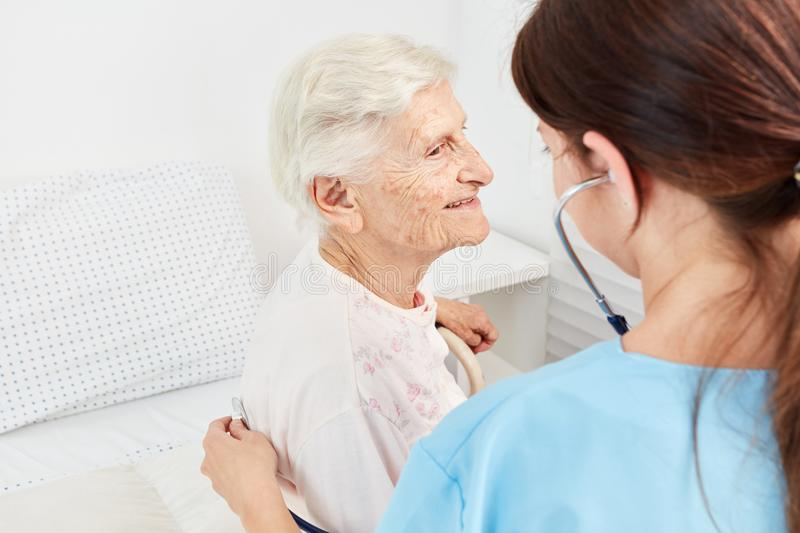 Caregiver examines old patient. Caregiver examines old female patient with stethoscope in nursing home royalty free stock photography