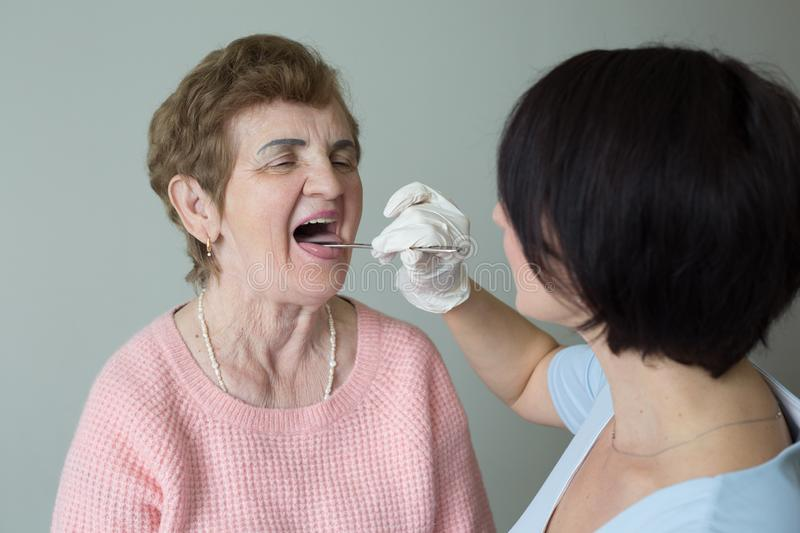 Caregiver female medical exam retired woman open mouth royalty free stock photography