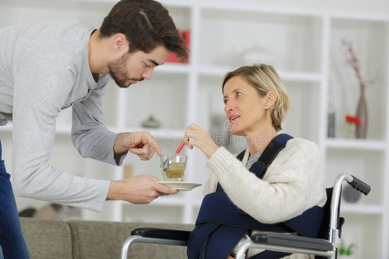 Caregiver giving cup tea to disabled woman in wheelchair. Caregiver giving cup of tea to disabled women in wheelchair stock photos