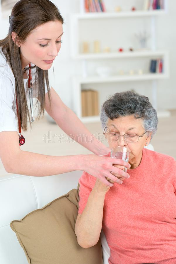 Caregiver giving water to old woman. Caregiver giving water to old women drink stock photos