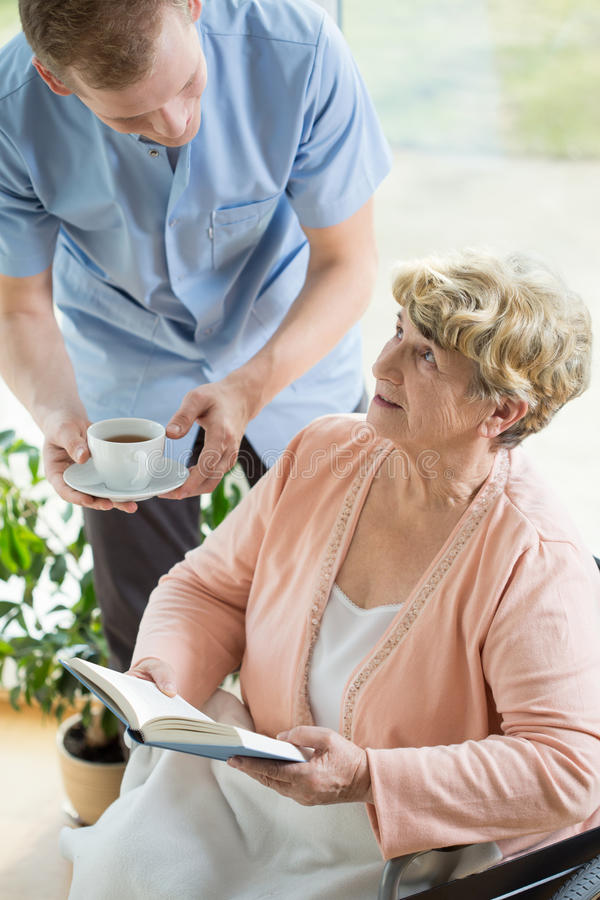 Caregiver helping disabled pensioner. Picture of caregiver helping disabled female pensioner stock photo