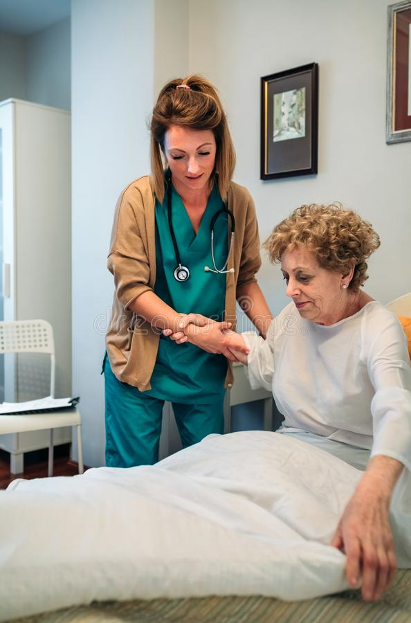 Caregiver helping elderly patient to get out of bed. Female caregiver helping elderly female patient to get out of bed stock images