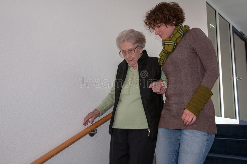 Senior woman going down stairs with helping hands of young woman royalty free stock photos