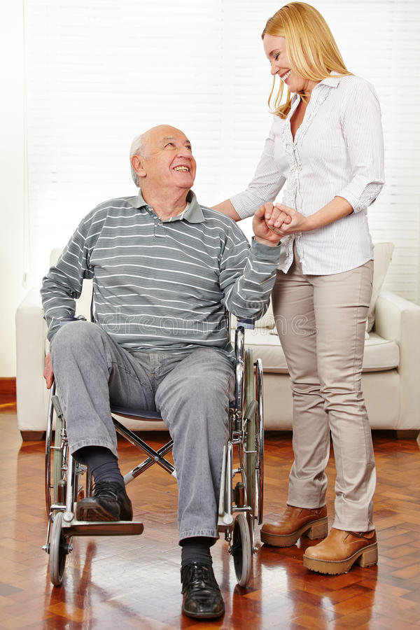 Caregiver helping senior citizen. Smiling caregiver helping senior citizen men in wheelchair standing up stock image