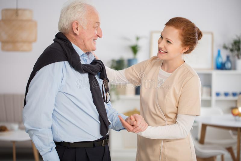 Caregiver helping senior man stock images