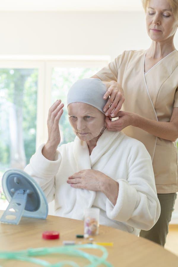 Caregiver helping senior woman with headscarf. Caregiver helping senior women with headscarf in the nursing house royalty free stock photos
