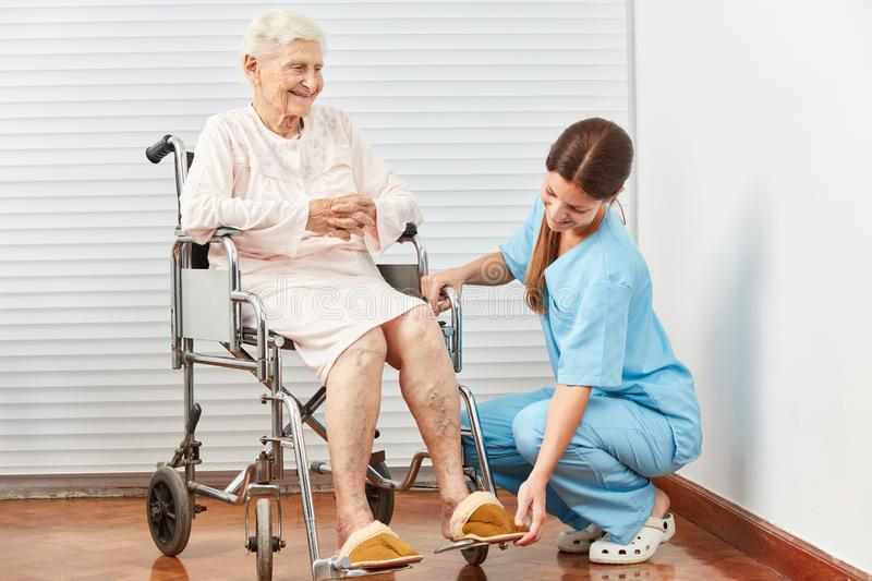 Caregiver helps handicapped woman in wheelchair royalty free stock image