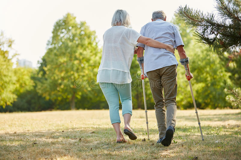 Caregiver helps man walking with crutches. Caregiver helps men walking with crutches in the nature royalty free stock photography