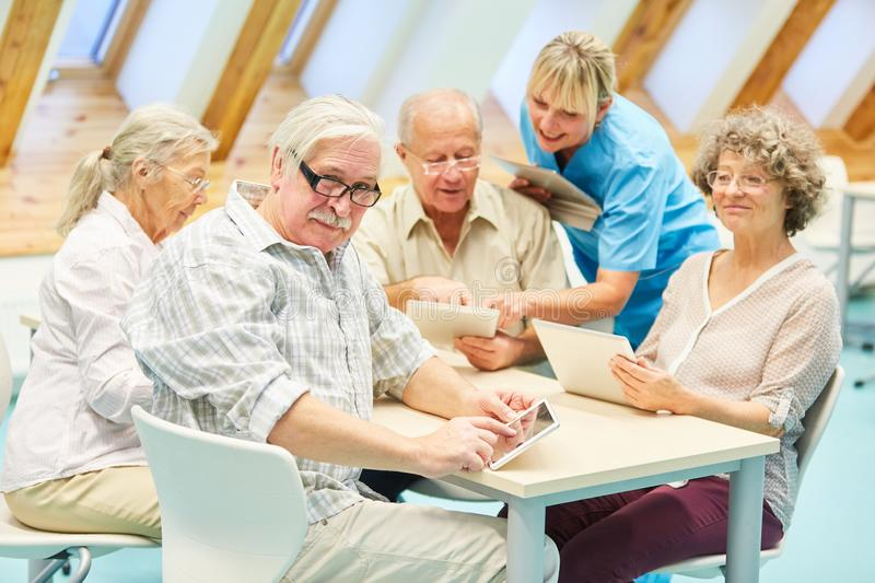 Caregiver helps seniors in computer course stock images