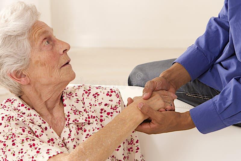 Caregiver holding elderly lady's hands cheerfully. Caregiver holding elderly lady's hands stock photo