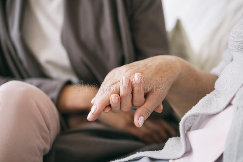 Caregiver holding the hand. Close up of caregiver holding older woman`s hand royalty free stock image