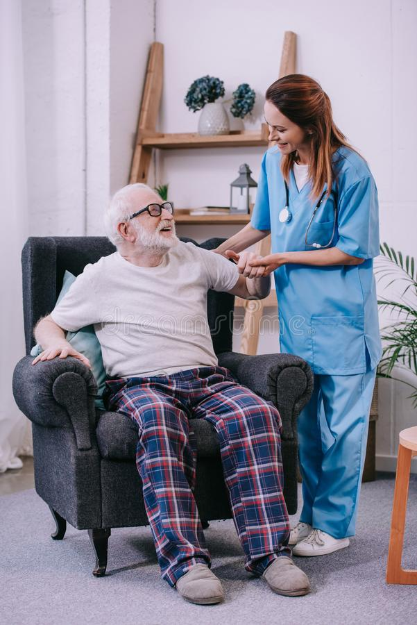 Caregiver holding hand of smiling senior man. Patient stock photos