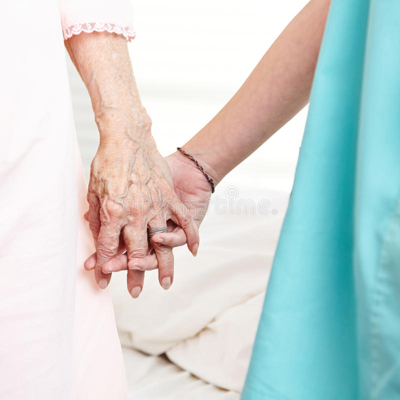 Caregiver holding hands of senior. Caregiver holding wrinkly hands of senior women at home stock photo