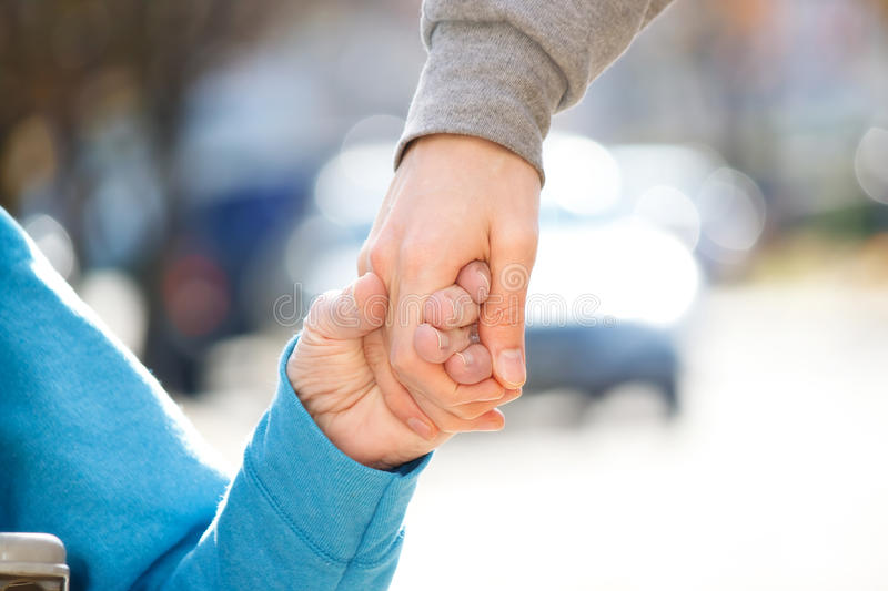 Caregiver Holding Senior's Hand. Young Caregiver Holding Senior's Hand Outside royalty free stock image