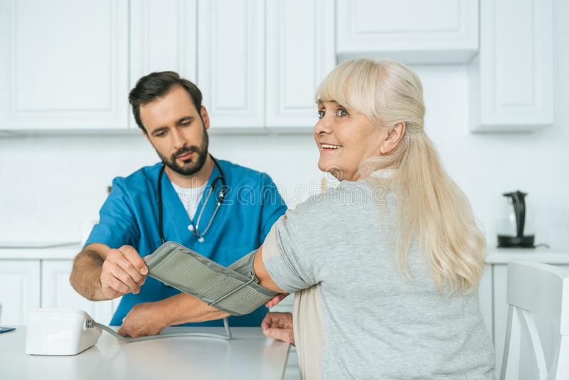 Caregiver measuring blood pressure to smiling. Senior woman royalty free stock photography