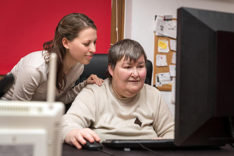 Caregiver and mentally disabled woman learning at the computer stock photo