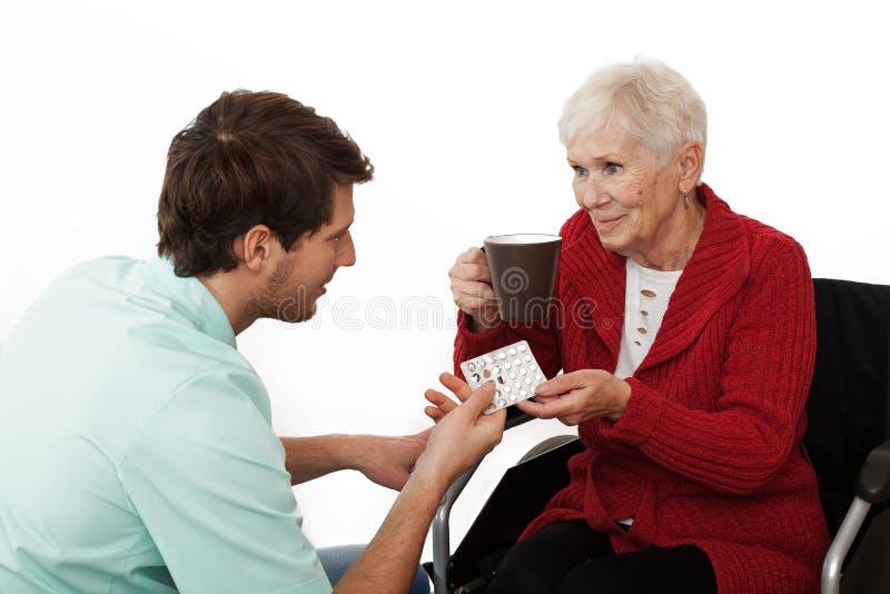 Caregiver. Nurse giving medicines to elder disabled person on wheelchair stock photos