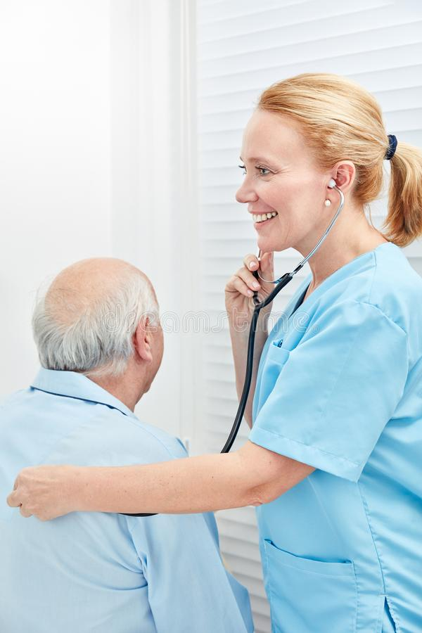 Nursing help listens to the patient with the stethoscope royalty free stock images