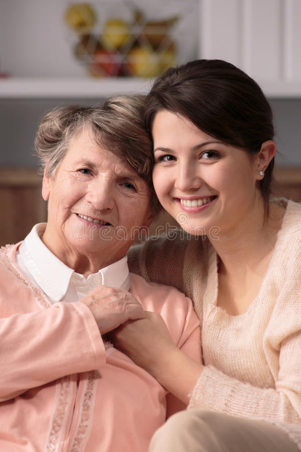 Caregiver and patient. Young pretty caregiver and older happy patient together royalty free stock photos