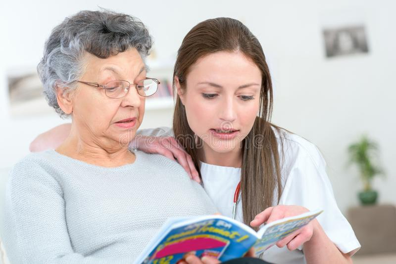 Caregiver reading book with elderly patient. Caregiver reading a book with an elderly patient stock images