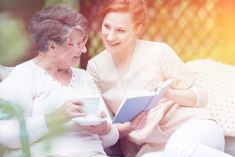 Caregiver and elderly woman. Caregiver reading a book and spending time with an elderly women on a terrace royalty free stock images
