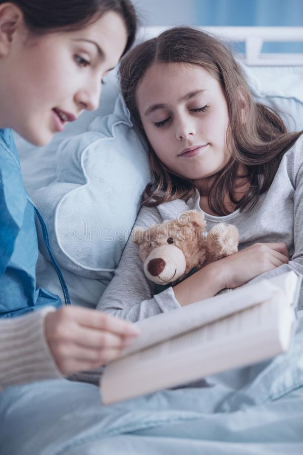 Caregiver reading a book to a sick girl with plush toy in the cl. Inic royalty free stock photo