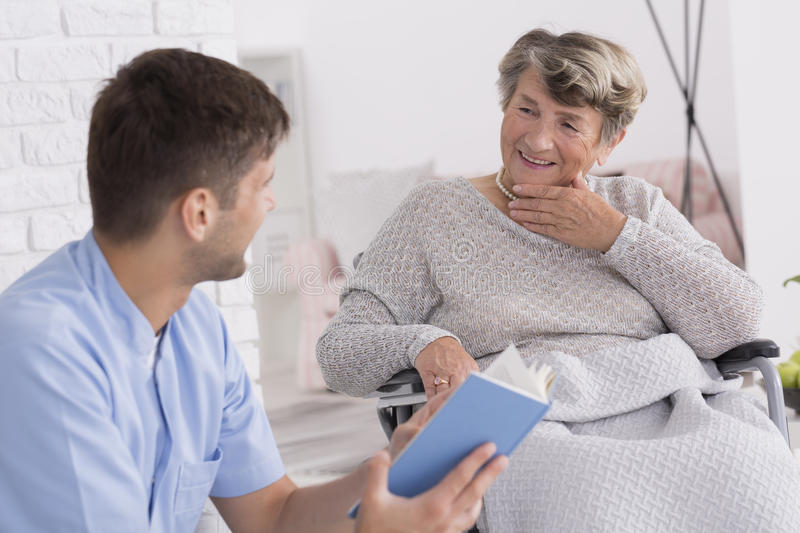 Caregiver reading for the elderly lady royalty free stock photography