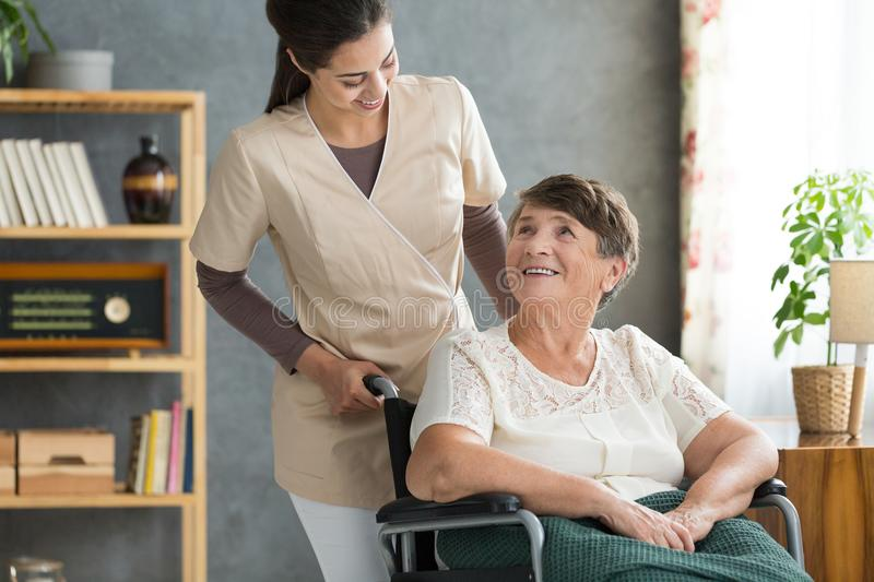 Caregiver in retirement home. Concerned caregiver checking up on her elder patient in cozy retirement home on a sunny day stock image