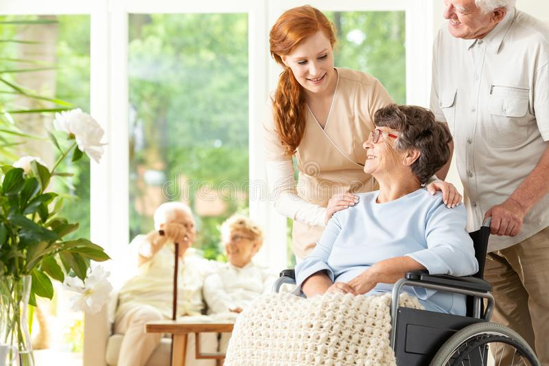 Caregiver and senior man supporting disabled elderly woman in th royalty free stock photography