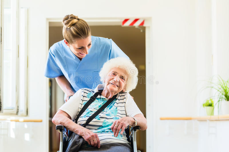 Caregiver with senior patient in wheel chair royalty free stock image