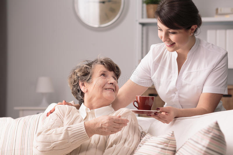 Caregiver serving the tea stock image