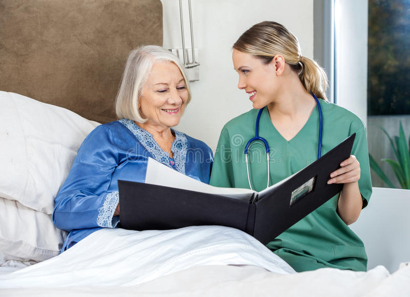 Caregiver Showing Medical Reports To Senior Woman. Smiling caregiver showing medical reports to senior women in bedroom at nursing home stock photography