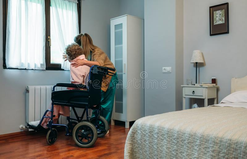 Caregiver showing the view through the window to elderly patient. Caregiver showing the view through the window to an elderly patient in a wheelchair stock image