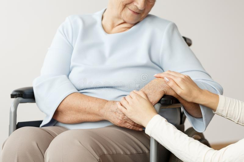 Caregiver supporting disabled pensioner. Close-up of caregiver supporting disabled pensioner in a wheelchair royalty free stock photography
