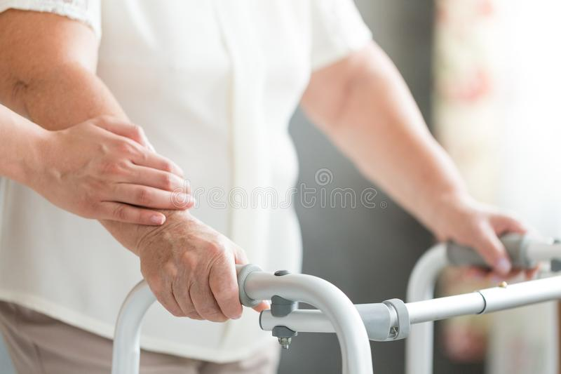 Caregiver supporting senior using walker. Close-up of caregiver supporting senior person sick with osteoporosis using walker at home stock photography