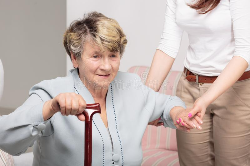 Caregiver supporting senior woman with walking stick stock photos