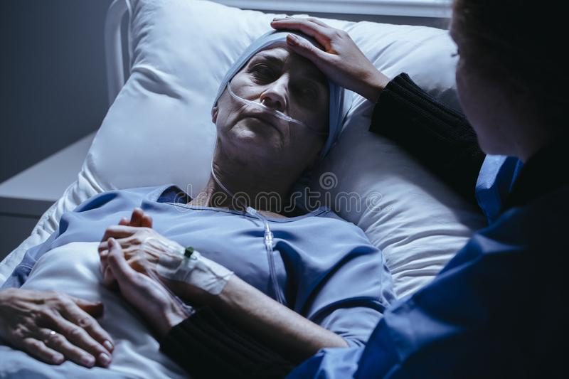 Caregiver supporting sick woman with cancer dying in the hospital royalty free stock photography