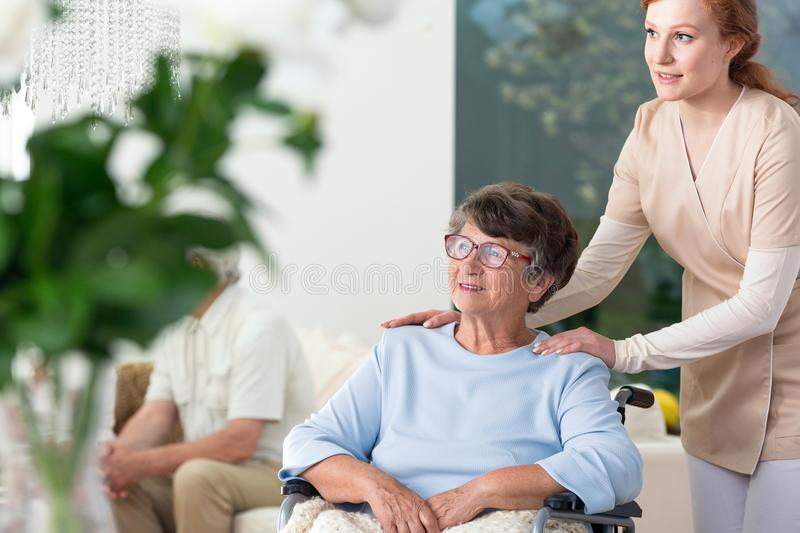 Caregiver taking care of disabled senior woman royalty free stock photo