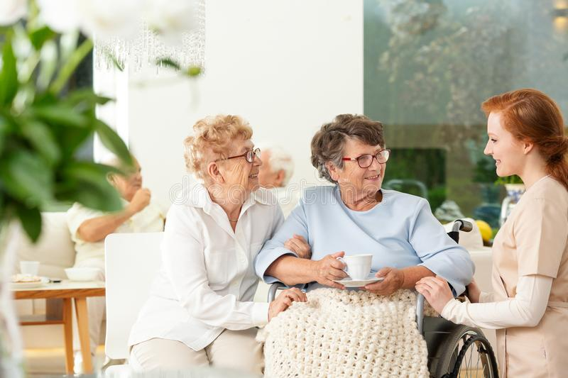 Caregiver talking to a smiling senior woman and her friend in th. Caregiver talking to a smiling senior women and her friend in the nursing house stock photography