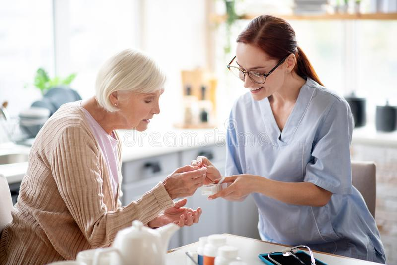 Caregiver wearing glasses giving vitamins to aged lady. Giving vitamins. Caregiver wearing glasses and uniform giving vitamins to aged lady royalty free stock photo