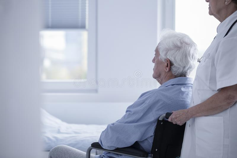 Caregiver supporting sick patient. Caregiver in white uniform helping sick patient in a wheelchair get to his bed stock image