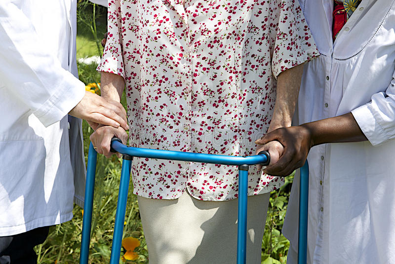Caregivers που βοηθά έναν ανώτερο ασθενή με τον περιπατητή της υπαίθριο στοκ φωτογραφία με δικαίωμα ελεύθερης χρήσης