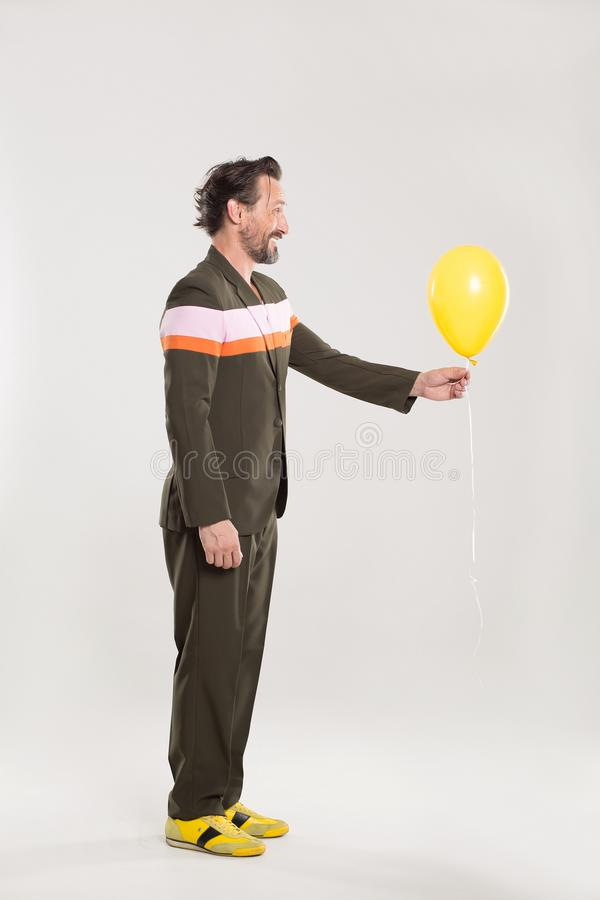 Happy man with yellow balloon. Careless man in black suit with red and white stripes. Holding yellow balloon stock images