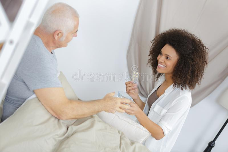 Carer administering medication to patient royalty free stock photo