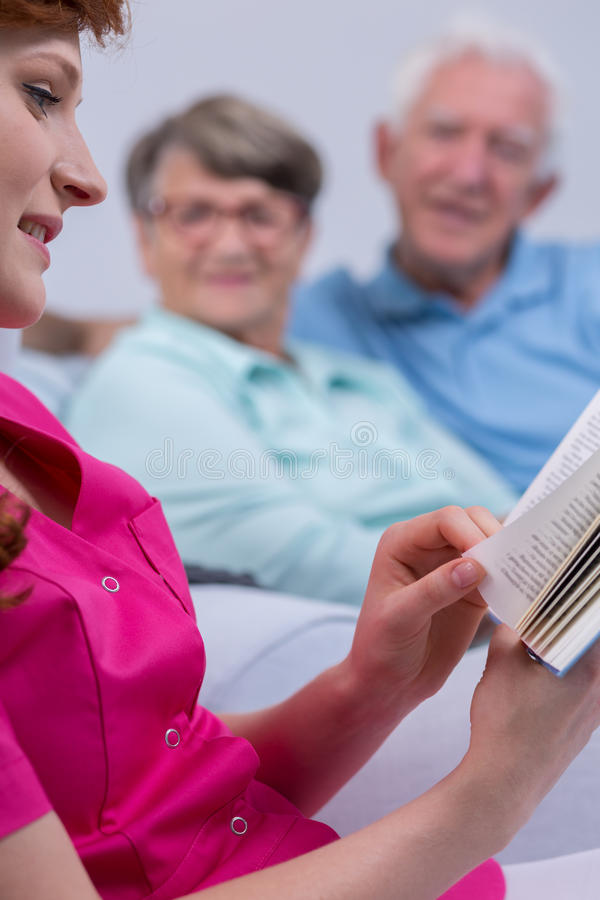 Carer with book. Senior men and women in background royalty free stock photo