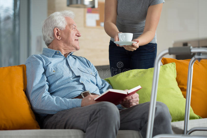 Carer giving disabled man coffee royalty free stock photo