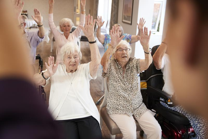 Carer Leading Group Of Seniors In Fitness Class In Retirement Home royalty free stock image